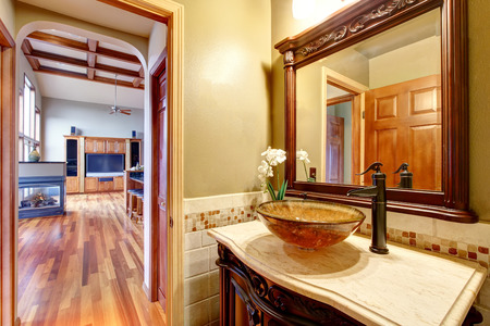 bathroom mirror: Bathroom interior in luxury house. Rich bathroom vanity cabinet with vessel sink and mirror. View living room. Northwest, USA