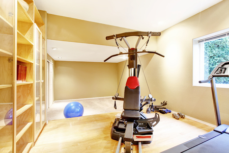 yellow walls: Yellow walls gym room with window. View of exercise equipments. Northwest, USA