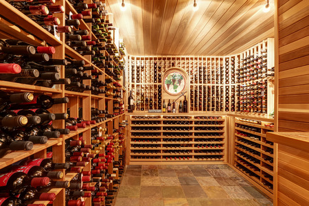 나무 저장 장치와 병 아치 밝은 홈 와인 저장고. 노스 웨스트, 미국