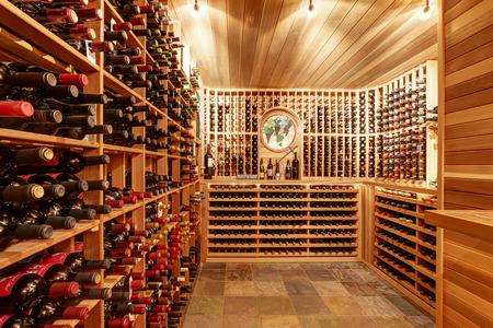 vino: Brillante bodega casa con unidades de almacenamiento de madera y arco con botellas. Noroeste, EE.UU. Foto de archivo