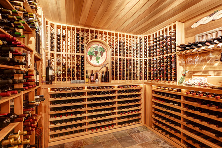 Bright home wine cellar with wooden storage units and arch with bottles. Northwest, USA