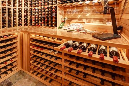 木製の収納ユニットとボトルとアーチで明るいホームなワインセラー。米国北西部