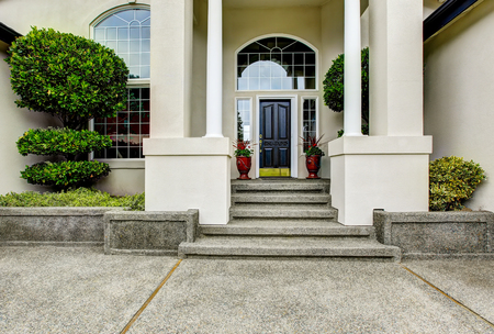 home exterior: Luxury house entry way exterior with concrete floor porch with columns. Northwest, USA Stock Photo