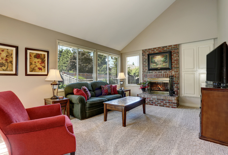 traditional living room: Traditional living room interior with green sofa and brick fireplace. Northwest, USA