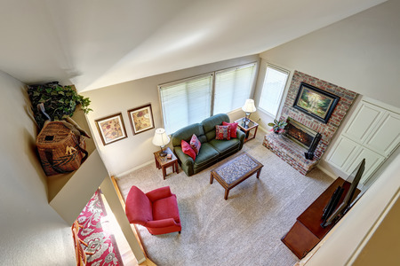 traditional living room: Top view. Traditional living room interior with green sofa and brick fireplace. Northwest, USA