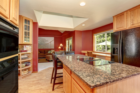 Kitchen room interior with red walls, granite counter top and bar stand. Northwest, USA