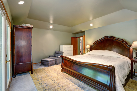 Bedroom interior with wooden king size bed and carpet floor. Northwest, USA