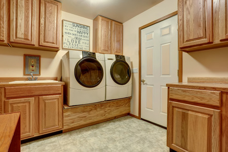 cabinets: Laundry room with wooden cabinets and tile floor. Northwest, USA Stock Photo