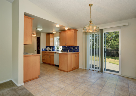 tile flooring: House interior. Maple kitchen cabinets with blue tile back splash trim, also beige tile flooring . Exit to the back yard. Northwest, USA Stock Photo