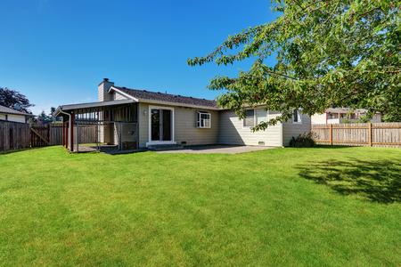 rambler: Fenced Backyard garden with cage and green grass.  American Rambler house exterior. Northwest, USA Stock Photo