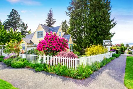 blancos: Pequeño exterior de la casa amarilla con la valla de estacas blanca y Puerta decorativa. Noroeste, EE.UU.