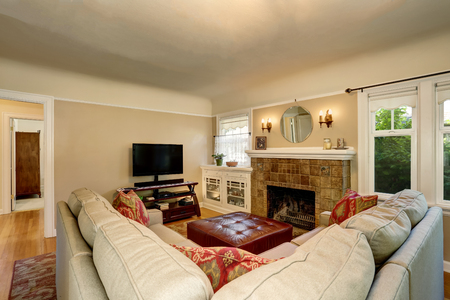 Cozy living room interior with brick fireplace, tv set and beige couch. Northwest, USA