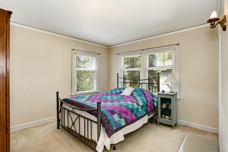 northwest: Bedroom interior with colorful bedding and carpet floor. Northwest, USA