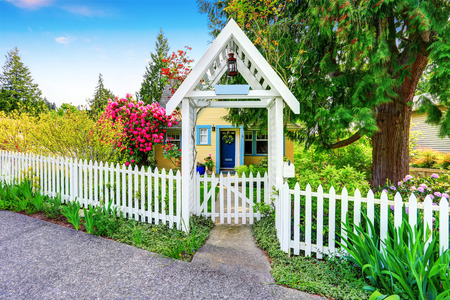 picket fence: Small Yellow house exterior with White picket fence and Decorative Gate. Northwest,USA