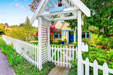 Small Yellow house exterior with White picket fence and Decorative Gate. Northwest,USA