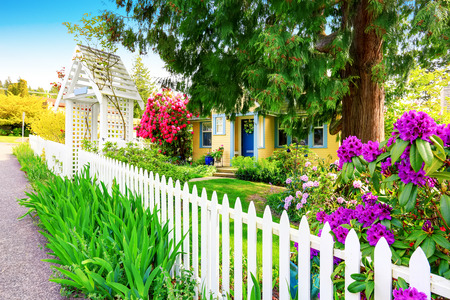picket: Small Yellow house exterior with White picket fence and Decorative Gate. Northwest,USA