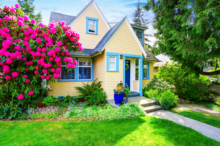 Small Yellow house exterior with blooming rhododendron in grass filled front garden. Northwest,USA Banco de Imagens