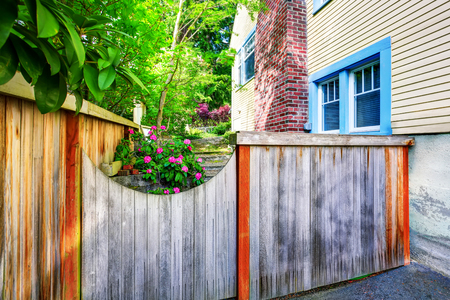 Wooden fence with gate to the backyard with side of the house. Northwest, USA