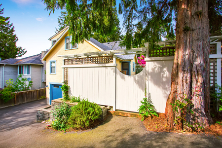 front house: Wooden fence with gate to the front garden. Yellow house exterior. Northwest, USA