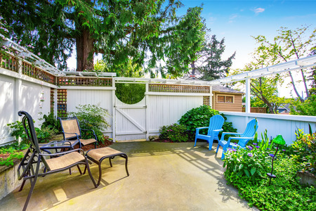 Yellow house backyard area with patio and white wooden fence. Northwest, USA