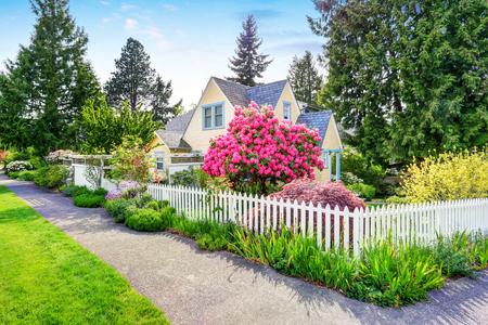 Kleine gele huis buitenkant met Witte piketomheining en bloeiende rododendron. Northwest, USA