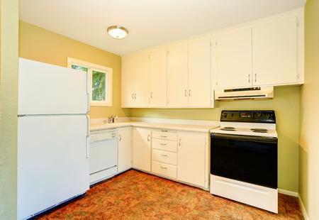 cocina vieja: interior de la cocina sencilla del viejo estilo con muebles y electrodomésticos blancos. Noroeste, EE.UU.