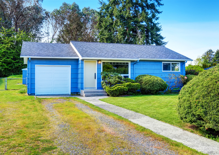 trimmed: Small cute blue house with driveway and trimmed hedges. Northwest, USA
