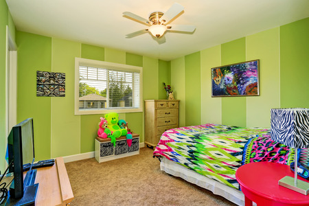 kids room: Adorable kids room in green color with bright colorful bedding and beige carpet  floor .Northwest, USA Stock Photo