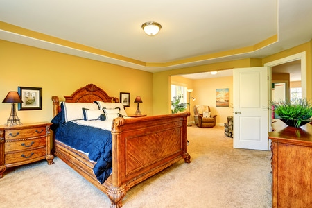 nightstand: Gorgeous Interior of master bedroom with carved wood bed with white and blue bedding, nightstand and carpet floor. Northwest, USA Stock Photo