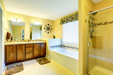 tile flooring: Luxury beige bathroom with wooden cabinet and two mirrors, white bath tub with tile trim, shower and tile flooring. Northwest, USA