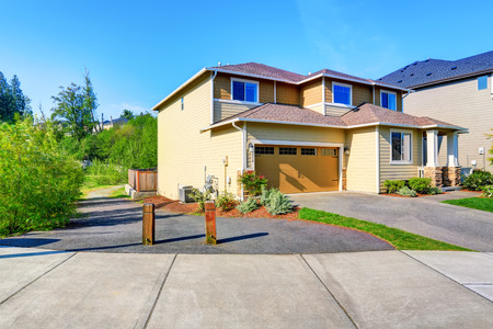 garage on house: Nice curb appeal of luxury beige house. Garage with concrete driveway. Northwest, USA Stock Photo