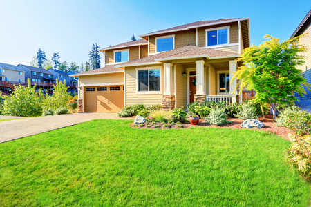 curb: Beautiful curb appeal of luxury beige house with well kept front garden. Northwest, USA