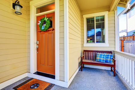 white trim: Cozy covered porch Close-up with front door and wooden bench with blue pillows. Northwest, USA Stock Photo