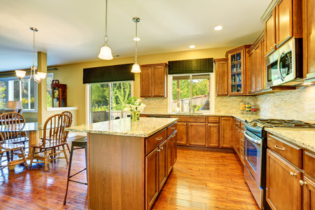 Wooden kitchen interior with kitchen island, steel appliances, granite counter tops and cabinets. Dining glass top table and wooden chairs. Northwest, USA