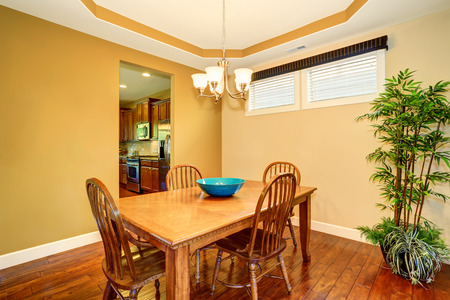 wooden houses: Dining wooden table and chair set. Dining room interior decorated with green tree in a pot. Northwest, USA