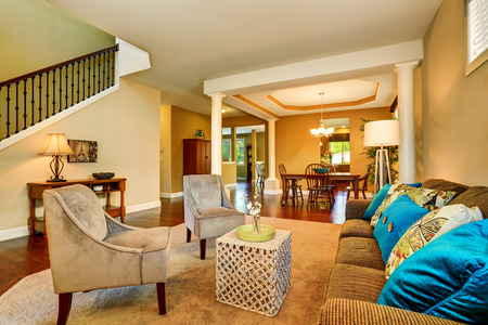 living room sofa: Open floor plan in luxury house . View of living room and dining room. Blue cushions on the sofa and two beige velvet armchairs in the living room. Northwest, USA Stock Photo