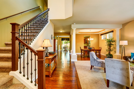 Open floor plan in luxury house . View of dining room, sitting room and entryway with staircase. Northwest, USA