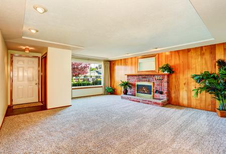 Leeg woon interieur met houten paneelmuur en open haard met baksteenbekleding. Noordwest, Verenigde Staten