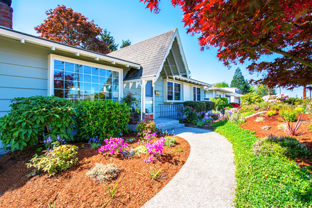Small light blue American house exterior with french windows. Walkway is decorated with nice flower beds. Northwest, USA