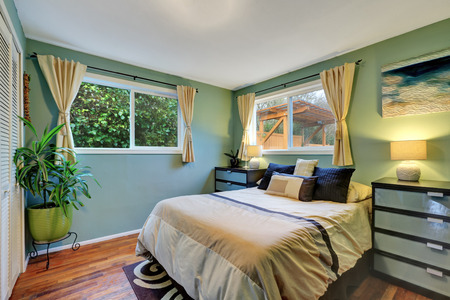 king size: Blue bedroom interior with king size bed, hardwood flooe and beige curtains. Northwest, USA