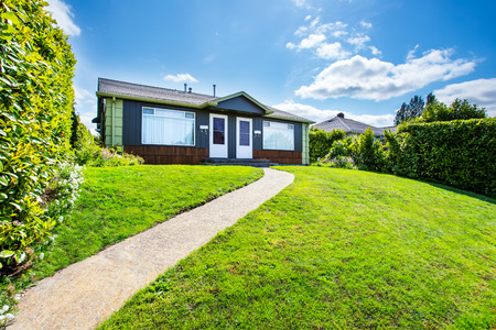 curb appeal: Small American two family house with concrete walkway, well kept lawn and green fence. Northwest, USA