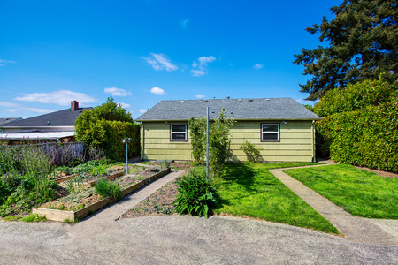 Backyard view of two family house with vegetable beds. Northwest, USA