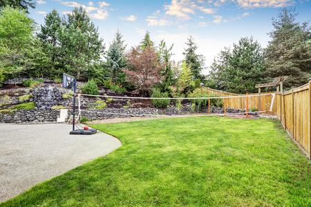 garden styles: Backyard well kept garden with rocks desing, basketball hoop and volleyball net. Northwest, USA Stock Photo