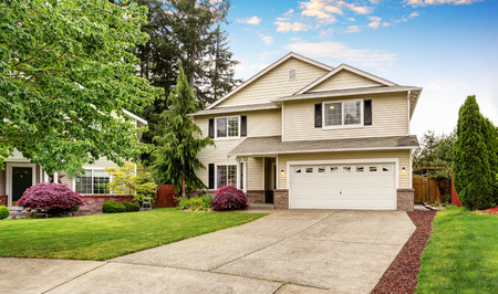 american house: American house exterior with siding trim, garage and well kept garden around. Northwest, USA Stock Photo