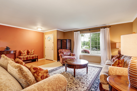 traditional living room: Traditional living room interior with beige walls, rug and white curtains. Northwest, USA