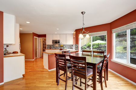 Dining area connected to kitchen room with tile counter top and hardwood floor. Open floor plan. Northwest, USA Stock Photo