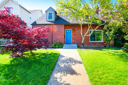 roofs: Red brick house with tile roof and maple tree in the front yard. Northwest, USA.