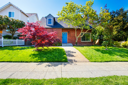 Red brick house with tile roof and maple tree in the front yard. Northwest, USA.