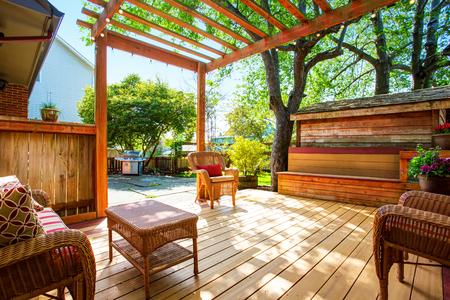 Backyard deck with wicker furniture and pergola. Northwest, USA