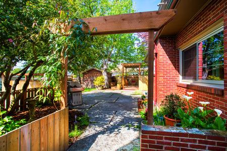 Opinión del patio trasero. La entrada al jardín y un patio. Noroeste, EE.UU. Foto de archivo - 61425597